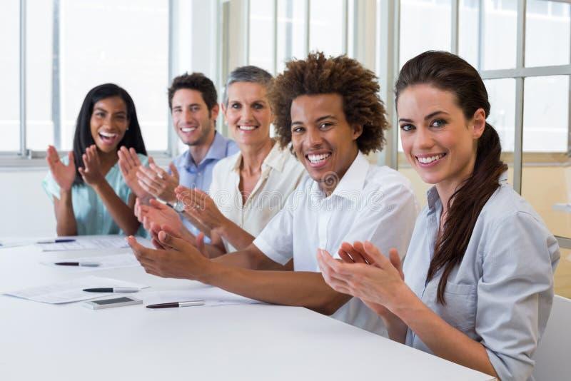 Geschäftsleute, die an der Kamera klatschen und lächeln lizenzfreie stockfotos