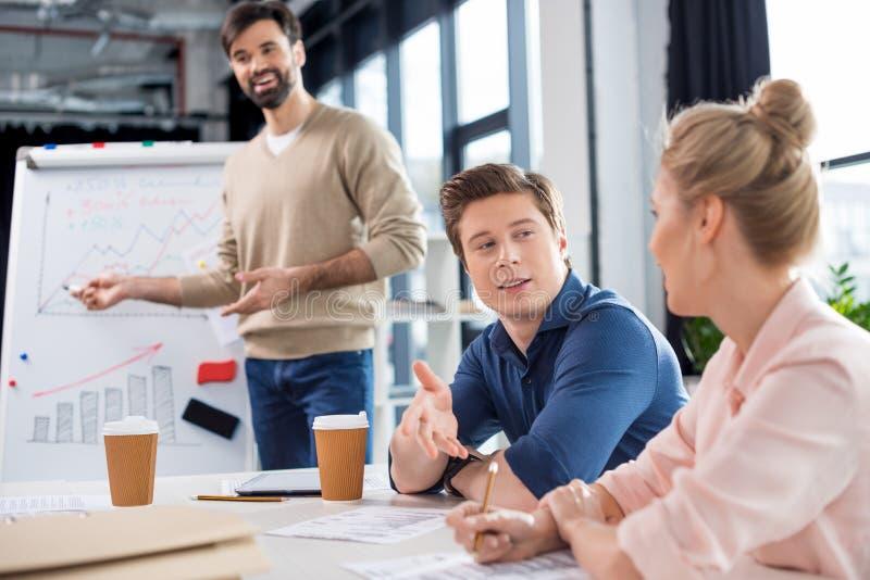 Geschäftsleute, die Diagramme und Statistiken über kleine Bürositzung besprechen stockbilder
