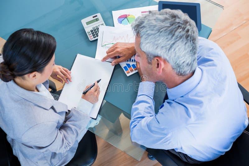 Geschäftsleute, die Dokumente mit Grafiken betrachten lizenzfreies stockfoto