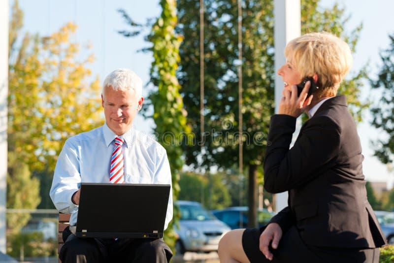 Geschäftsleute, die draußen arbeiten stockbild