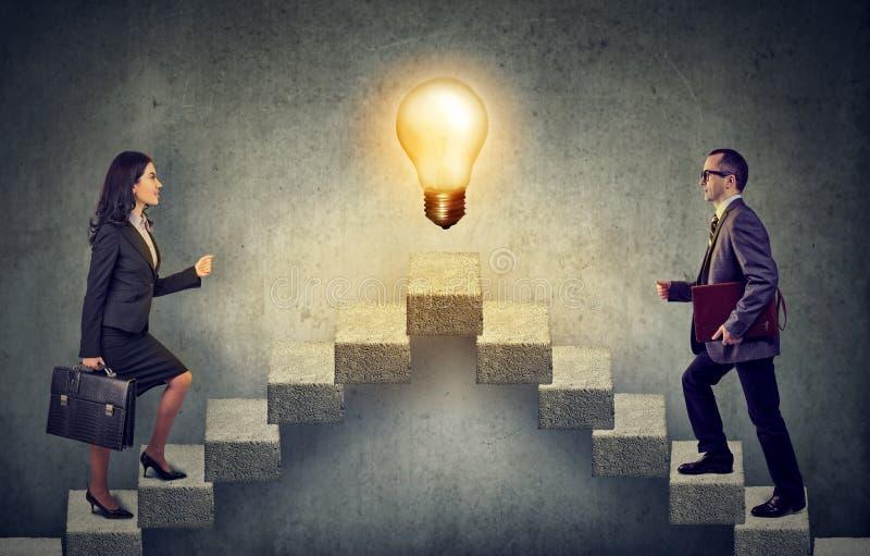 Geschäftsleute, die eine Treppenhauskarriereleiter mit Glühlampe der Idee auf eine Oberseite steigernd klettern lizenzfreie stockfotos