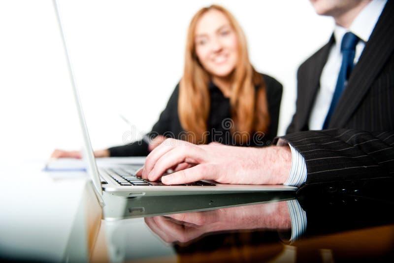 Geschäftsleute, die an einem Laptop arbeiten und schreiben lizenzfreies stockfoto