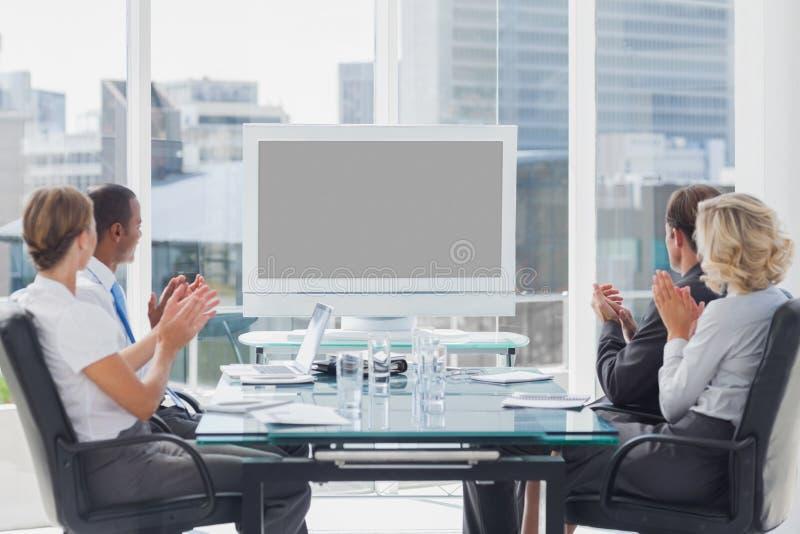 Geschäftsleute, die an einem Schirm applaudieren lizenzfreie stockbilder