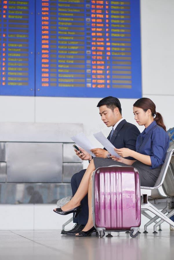 Geschäftsleute, die in Flughafen warten lizenzfreie stockbilder