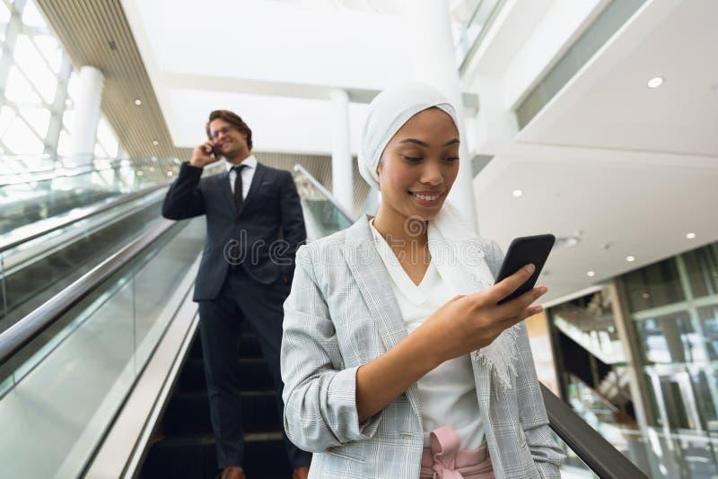 Geschäftsleute, die Handy auf Rolltreppe in einem modernen Büro verwenden lizenzfreie stockbilder