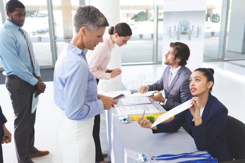 Geschäftsleute, die herein am Konferenzausrichtungstisch überprüfen stockbilder