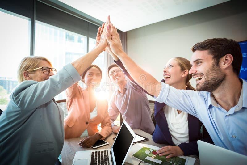 Geschäftsleute, die Hoch fünf am Schreibtisch geben lizenzfreies stockbild