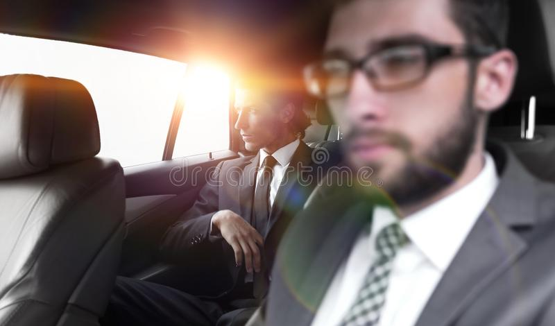 Geschäftsleute, die im Auto sitzen stockbild