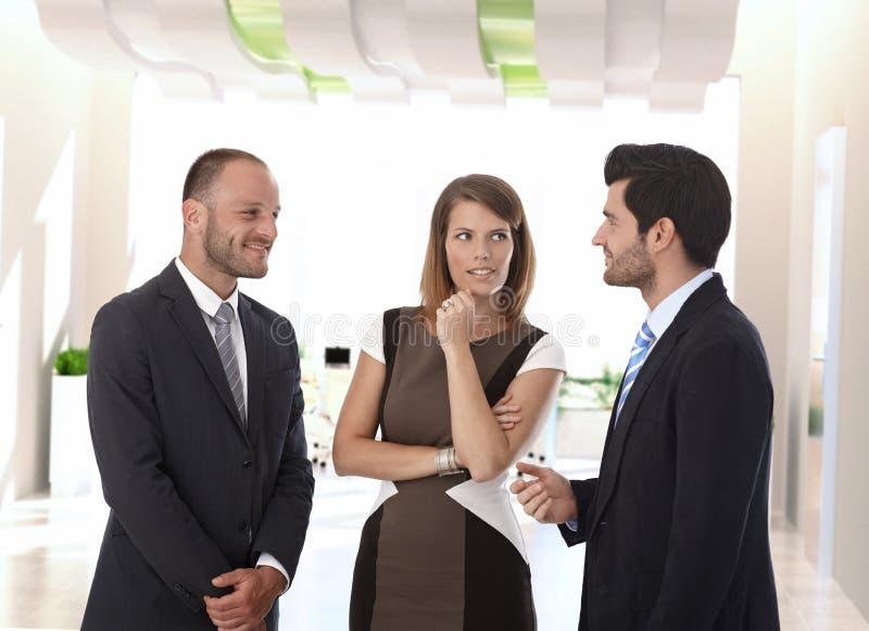Geschäftsleute, die im Bürokorridor sprechen stockfotografie