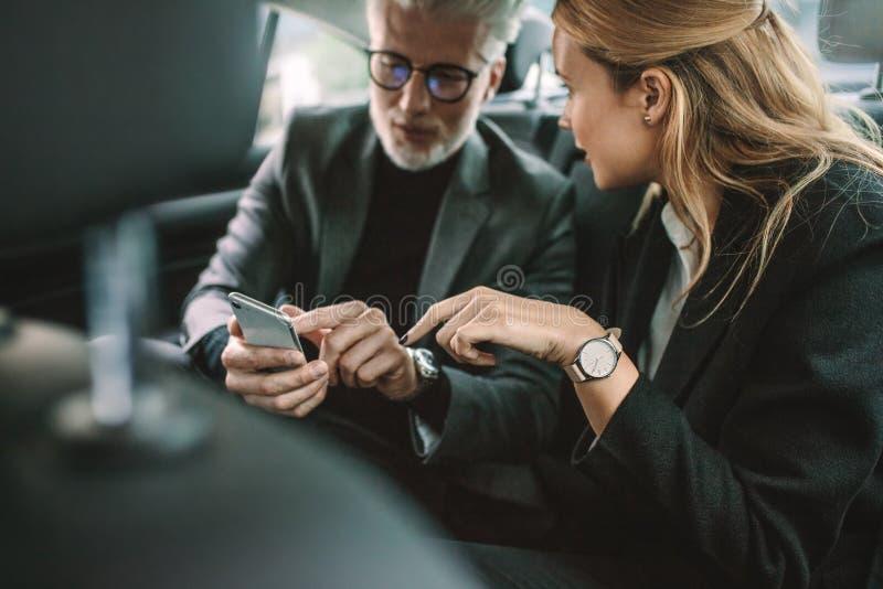 Geschäftsleute, die intelligentes Telefon im Taxi verwenden stockbild