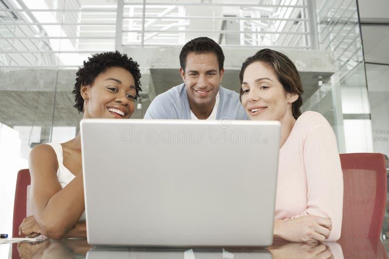 Geschäftsleute, die Laptop am Konferenztische verwenden stockfoto