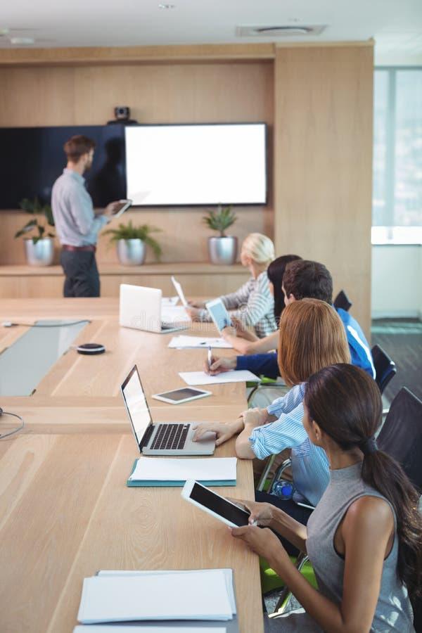 Geschäftsleute, die Laptop und digitale Tabletten am Konferenztische während der Sitzung verwenden stockfotografie