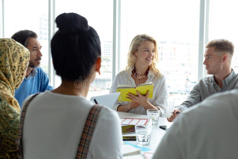 Geschäftsleute, die mit einander beim Treffen am Konferenzsaal in einem modernen Büro sich besprechen lizenzfreie stockfotos