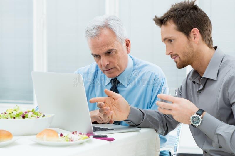 Geschäftsleute, die am Mittagessen arbeiten stockfoto