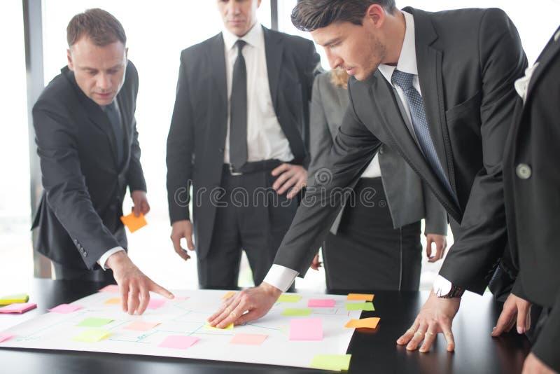 Geschäftsleute, die Plan auf Schreibtisch entwickeln lizenzfreies stockfoto