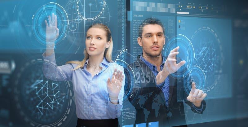 Geschäftsleute, die Projektionen des virtuellen Schirmes verwenden lizenzfreie stockbilder