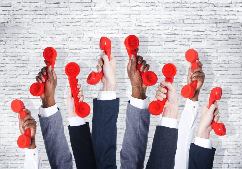Geschäftsleute, die rotes Telefon halten lizenzfreie stockfotografie