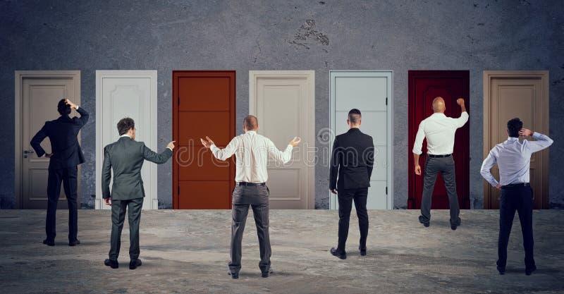 Geschäftsleute, die schauen, um die rechte Tür vorzuwählen Konzept der Verwirrung und des Wettbewerbs lizenzfreie stockbilder
