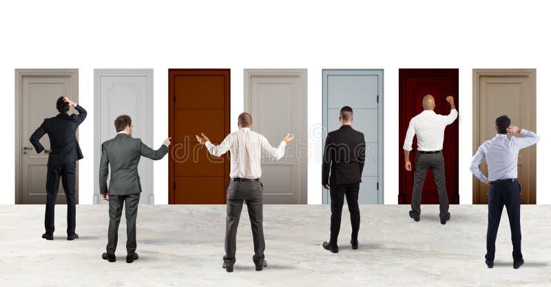 Geschäftsleute, die schauen, um die rechte Tür vorzuwählen Konzept der Verwirrung und des Wettbewerbs stockfotos