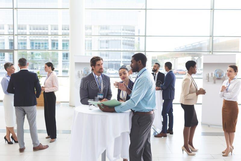 Geschäftsleute, die sich bei Tisch über Dokumenten während eines Seminars besprechen lizenzfreies stockbild