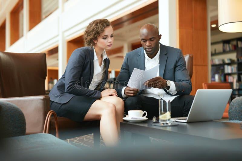 Geschäftsleute, die sorgfältig einen Vertrag lesen stockbilder