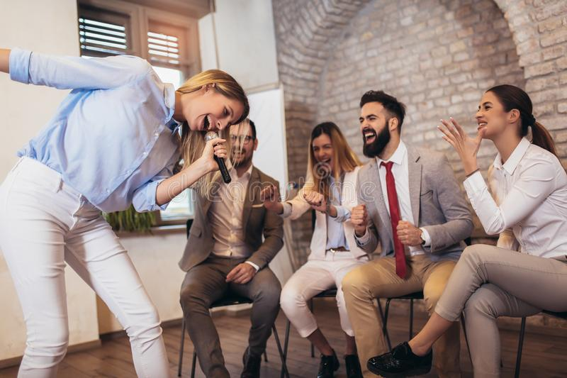 Geschäftsleute, die Teamschulungsübung während des Teamentwicklungsseminar-Gesangkaraokes machen stockfotos