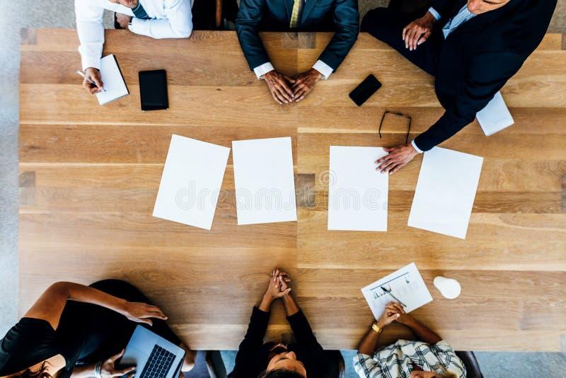 Geschäftsleute, die um eine Tabelle mit Leerbelegen sitzen stockfotos