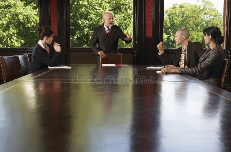 Geschäftsleute, die um Sitzungssaal-Tabelle sich treffen stockbilder