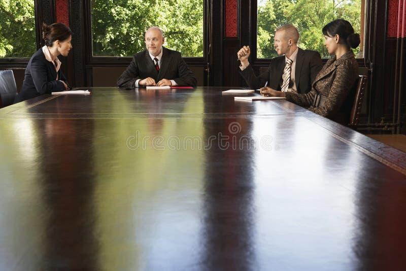 Geschäftsleute, die um Sitzungssaal-Tabelle sich treffen stockfotos