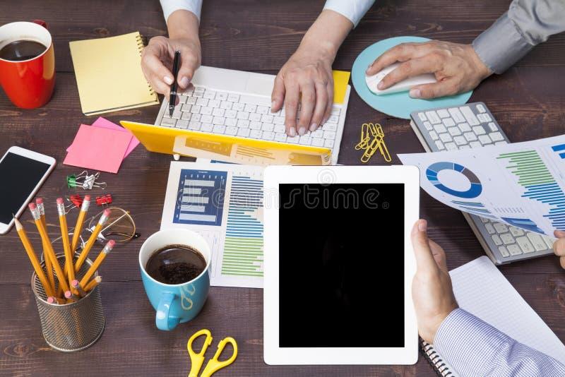 Gesch?ftsleute, die unter Verwendung der Laptop-Computers, Tabletten-PC, Zeichenpapier mit Ma?einteilung f?r AnalyseGesch?ftsstra lizenzfreie stockfotos