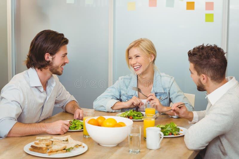 Geschäftsleute, die während des Mittagessens lachen stockbilder