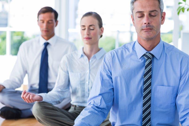 Geschäftsleute, die Yoga auf Boden tun stockfotografie