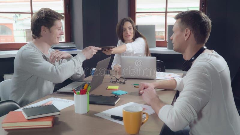 Geschäftsleute, die zuhause unter Verwendung der Geräte sprechen lizenzfreie stockfotografie