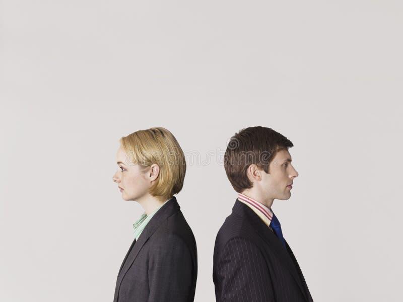 Geschäftsleute, die zurück zu Rückseite auf Gray Background stehen lizenzfreie stockfotografie