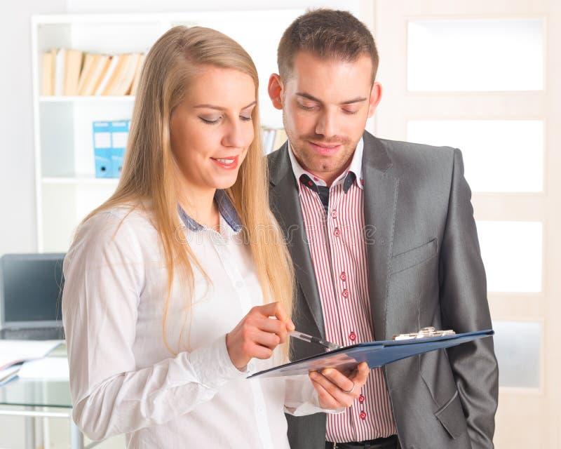 Geschäftsleute, die zusammen ein Dokument lesen stockfotos