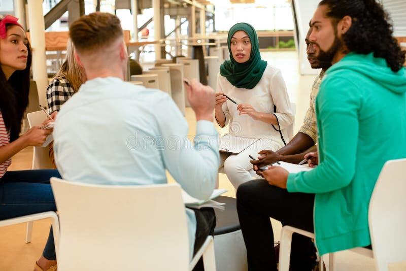 Geschäftsleute, die zusammen sitzen und eine Gruppendiskussion in einem modernen Büro haben stockfoto