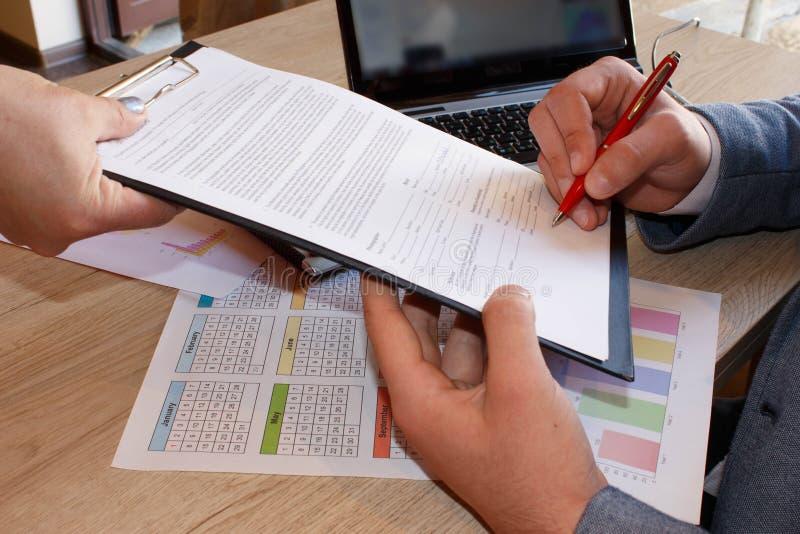 Geschäftsleute, die Zustimmungsvertrag schreiben stockbilder