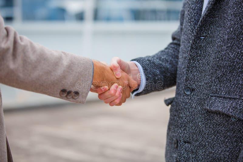Geschäftsleute in einem Mantel auf dem Pier rütteln Hände lizenzfreies stockbild