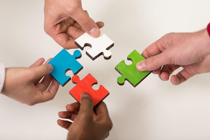 Geschäftsleute gruppieren zusammenbauendes Puzzlen und stellen Teamunterstützung dar lizenzfreie stockfotografie