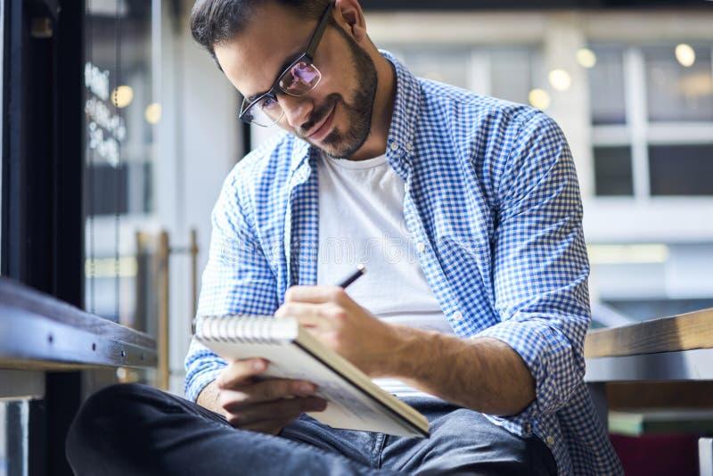 Geschäftsleute im blauen Hemd unter Verwendung des Stiftes beim Sitzen durch Fenster lizenzfreie stockfotografie