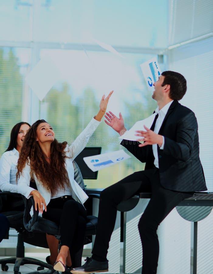 Geschäftsleute regten glückliches Lächeln, Wurfsdokumente fliegen in einer Luft auf lizenzfreies stockbild