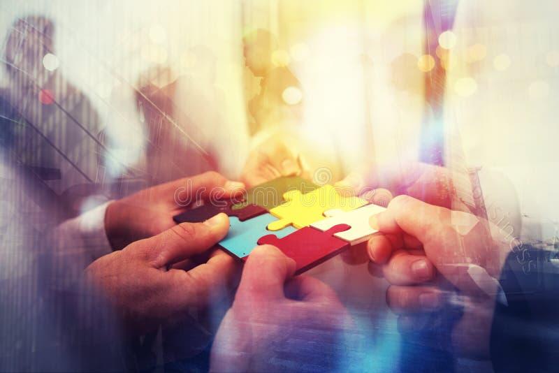 Geschäftsleute schließen sich Puzzlespielstücken im Büro an Konzept der Teamwork und der Partnerschaft Doppelbelichtung mit Licht lizenzfreie stockfotografie