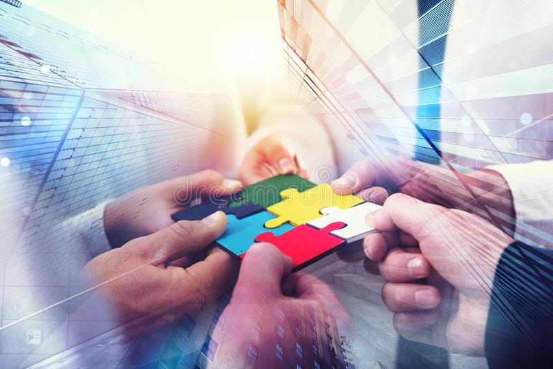 Geschäftsleute schließen sich Puzzlespielstücken im Büro an Konzept der Teamwork und der Partnerschaft Doppelbelichtung mit Licht stockfoto