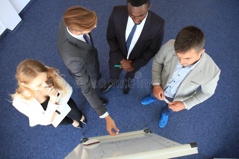 Geschäftsleute team an der Darstellung, die mit Diagrammen und diargams am flipchart arbeitet Beschneidungspfad eingeschlossen lizenzfreie stockfotografie