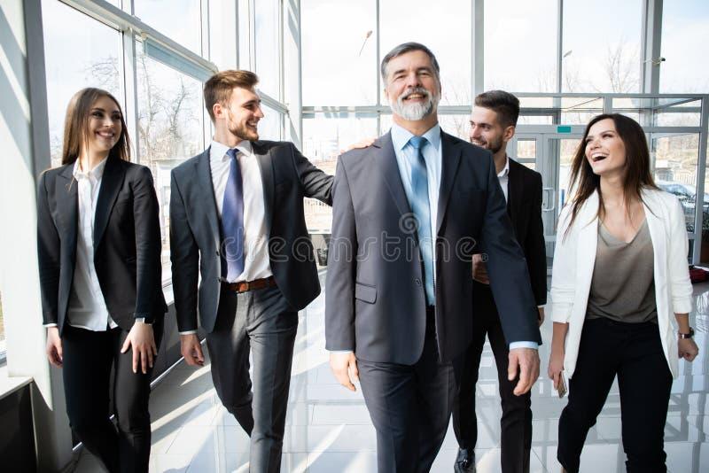 Geschäftsleute Team Walking In Modern Office, überzeugte Geschäftsmänner und Geschäftsfrauen mit reifem Führer In Foreground stockfoto