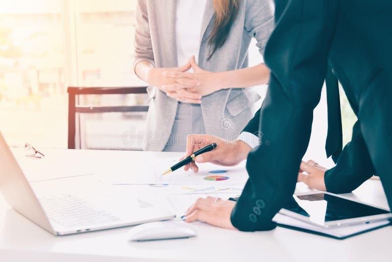 Geschäftsleute, welche die Diagramme und die Diagramme besprechen: Geschäftsteam-Geistesblitzkonzept lizenzfreies stockbild