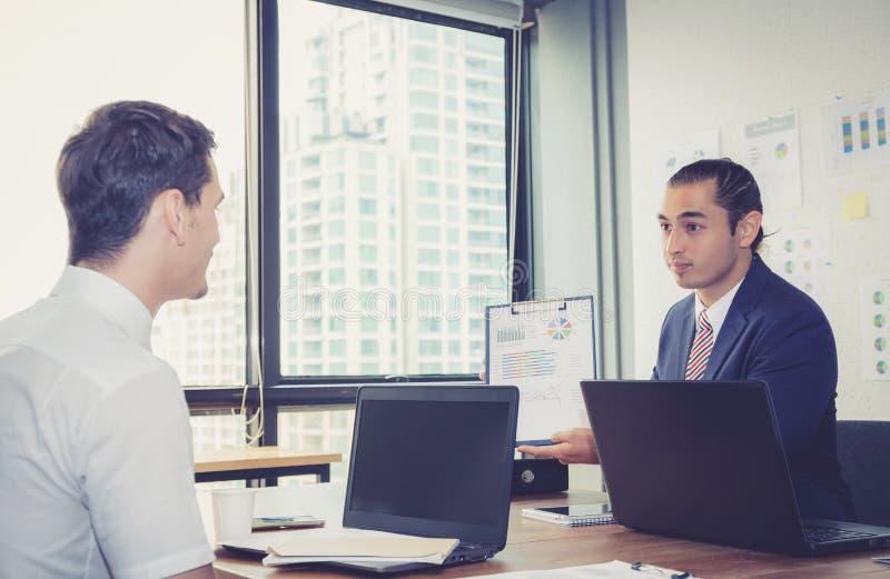 Geschäftsleute, welche die Diagramme und die Diagramme zeigen die Ergebnisse besprechen stockfotos