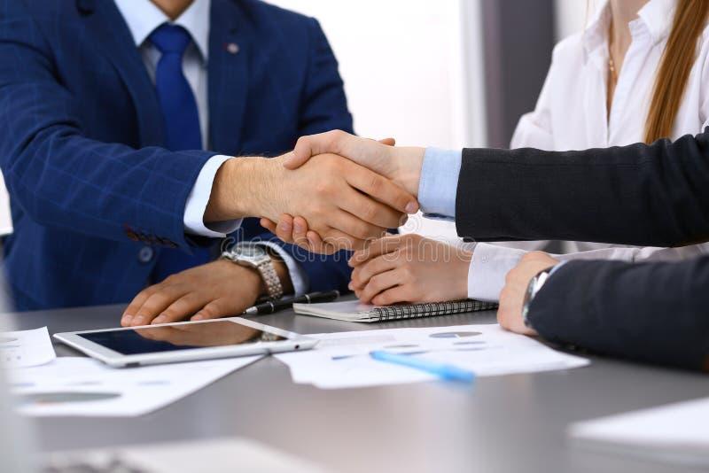 Geschäftsleute, welche die Hände, ein Papierunterzeichnen oben beendend rütteln Beratungskonzept der Sitzung, des Vertrages und d stockbilder