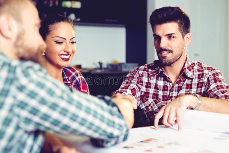 Geschäftsleute, welche die Hände, eine Sitzung oben beendend rütteln stockfoto