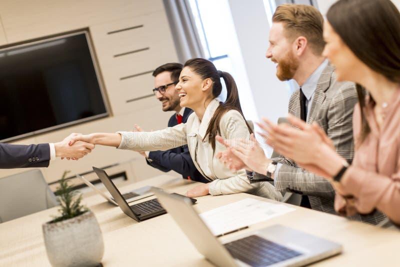 Geschäftsleute, welche die Hände oben beenden eine Sitzung im Büro rütteln stockfoto